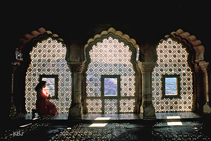 A young tourist looking out through the 'Jharokhas' (narrow windows)  of Amer Palace in Rajasthan, India.