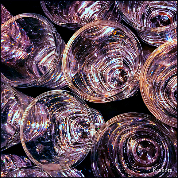 Sparkling glasses at a cocktail party waiting to be filled. Colorful lights all around are reflecting on their surfaces.
