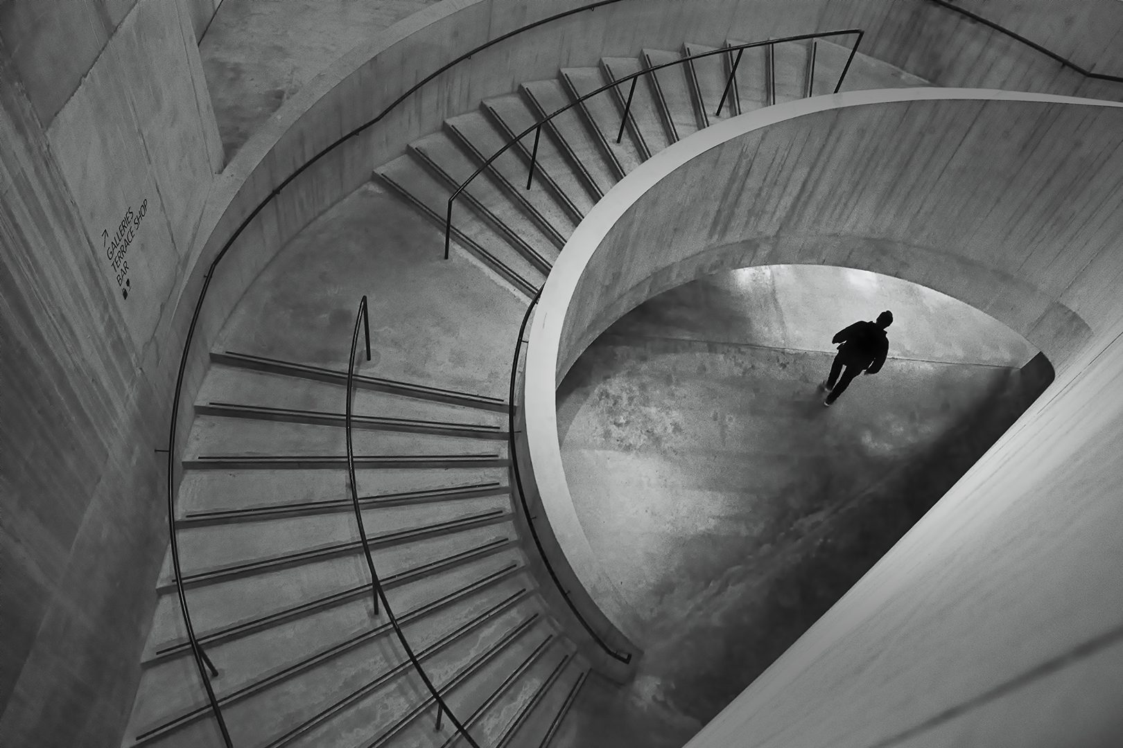 This picture, a man walking under the winding stairway was captured on 12 February 2020 at Tate Modern. The number of visitors was relatively less due to COVID 19 threat.  It was around 4 pm that I noticed this frame and I wanted a person in a black outfit to cross this point to contrast against the light patch on the floor.  After a wait of about 30 minutes, the right person came and I was successful in capturing the moment giving the feeling of exit.